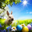 Art Little Easter bunny and Easter eggs on green grass - Stock Photo