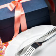 Dinner plates and cutlery with a gift — Stock Photo