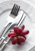 Place setting with fresh grapes — Stock Photo