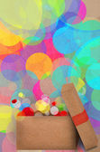 Gift on a bokeh of colourful party lights — Stock Photo