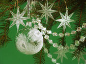 White christmas tree decorations on green — Stock Photo
