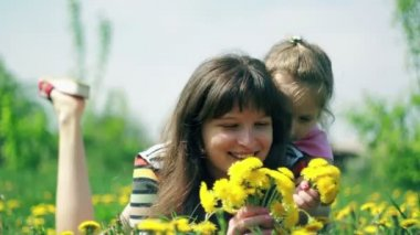 Daughter gives mom smell the bouquet of dandelions — Vídeo de stock