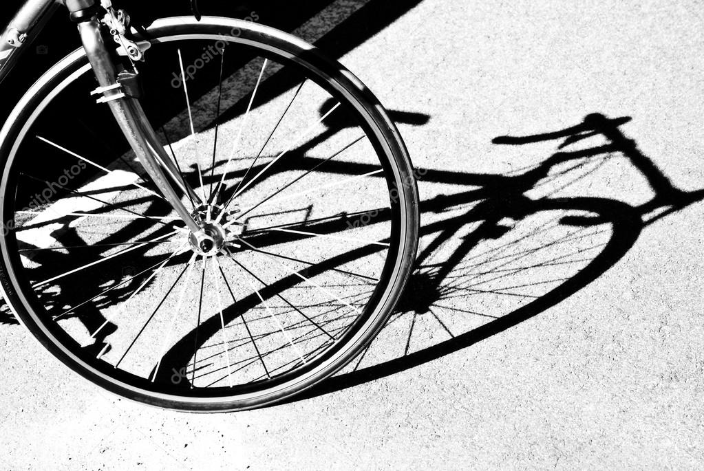 A bicycle wheel and silhouette in black and white. — Stock Photo #13819103