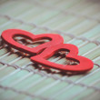 Two red hearts on bamboo napkin — Stock Photo