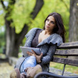 Stock Photo: Young woman with tablet on the bench