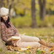 Young woman with a book in the forest — Stock Photo