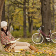 Stock Photo: Young woman reading in the autumn forest