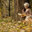 Young woman reading in the autumn forest — Stock Photo #16810105