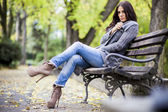Young woman on the bench in the park — Stok fotoğraf
