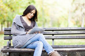 Young woman with tablet on the bench — Foto de Stock