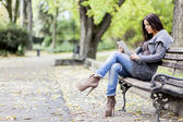 Young woman with tablet on the bench — Stock Photo