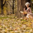 Young woman reading in the autumn forest — Stock Photo #18328571
