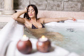 Pretty young woman relaxing in the hot tub — Stockfoto