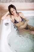 Pretty young woman relaxing in the hot tub — Stock Photo