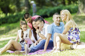 Teenagers in the park with tablet — Stock Photo