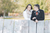 Young couple by the wooden fence — Stock Photo