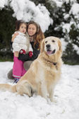 Family with a dog at snow — Stock Photo