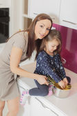 Mother and daughter in the kitchen — Stockfoto