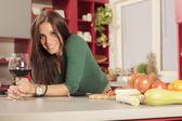 Mujer joven en la cocina con un vaso de vino tinto — Foto de Stock