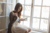 Young woman reading by the window — Stock Photo