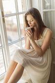 Jolie jeune femme par la fenêtre — Photo