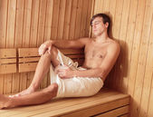 Young man relaxing in the sauna — Stok fotoğraf
