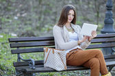 Young woman with tablet in the park — Stockfoto