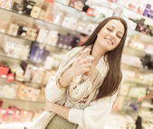 Pretty young woman in perfumery — Stock Photo