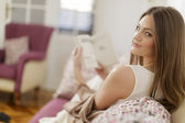 Young woman reading a book in the room — Stock Photo
