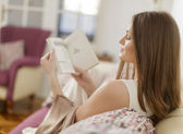 Young woman reading a book in the room — Stockfoto