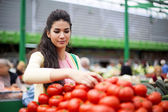 Pretty young woman buying vegetables on the market — Stock Photo
