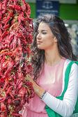 Ung kvinna köpa grönsaker på marknaden — Stockfoto