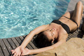Woman lying by the pool — Stock Photo