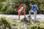 Young couple hiking by the river — Stock Photo