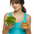 Woman making decision between healthy salad and fast food — Stock Photo #20067071