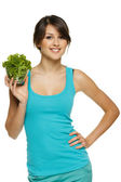 Woman holding lettuce leaves in transparent bowl — Stock Photo