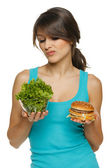 Woman making decision between healthy salad and fast food — Stock Photo