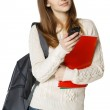 Student with backpack and books sending a sms on cell phone — Stock Photo