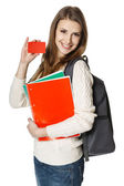 Woman wearing a backpack and holding notebooks showing blank credit card — Stock Photo