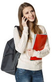 Student with backpack and books talking on cell phone — Stock Photo