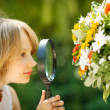 Girl exploring flowers through the magnifying glass - Stock Photo
