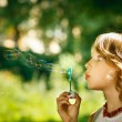 Girl blowing soap bubbles — Stock Photo #24260277