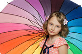Little girl standing under colorful umbrella — Stock Photo