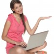 Smiling casual female sitting with laptop on the floor — Stock Photo