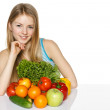 Woman sitting at the table with vegetables — Stock Photo #31684013
