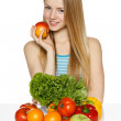 Woman sitting at the table with vegetables — Stock Photo #31685195