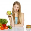 Woman sitting between healthy food and fast food — Stock Photo