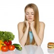 Woman making decision between healthy food and fast food — Stock Photo