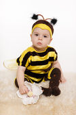 Baby earing bee costume sitting on the floor — Stock Photo