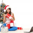 Girl sitting near Christmas tree with many gifts and laptop — Stock Photo